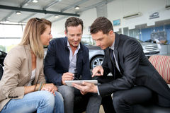 Couple making a digital signature on tablet in car shop Royalty Free Stock Image