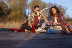 Couple making dinner while camping. Couple in love on an outdoor camping adventure, making dinner at a lake docks and enjoying a beautiful day in nature royalty free stock image