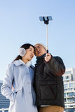 Couple making face and clicking pictures using selfie stick Stock Images