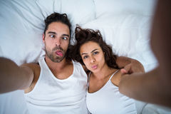 Couple making faces while taking self portrait Royalty Free Stock Image