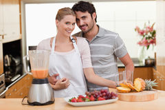 Couple making fresh fruits juice Royalty Free Stock Image