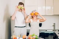 Couple making fresh organic juice in kitchen together royalty free stock photography