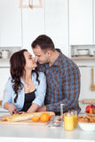 Couple making fresh organic juice in kitchen together. A young woman in a blue shirt slices a baguette. A man is hugging Stock Image