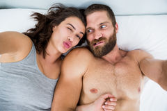 Couple making funny faces on bed Stock Photos