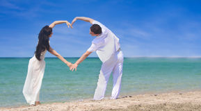 Couple making heart by arms on beach Royalty Free Stock Photo