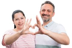 Couple making heart gesture with hands. Man and women couple smiling and making heart gesture with hands as love concept isolated on white studio background stock images