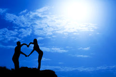 Couple making heart shape with arms. Against blue sky Royalty Free Stock Photography