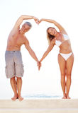 Couple making heart shape with arms by the pool Royalty Free Stock Images