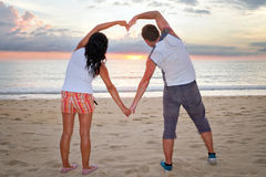 Couple making heart shape with arms at sunset Royalty Free Stock Photos