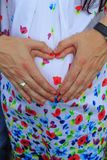A couple making a heart shape on the pregnant belly with their hands. Concept of pregnancy,. Expecting a baby, love, care stock photo