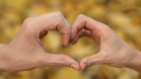 Couple making heart sign by hands, crossing fingers, symbol of love connection. Stock footage stock video footage