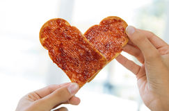 Couple making heart sign with two slices of bread with jam Stock Images