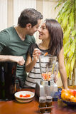 Couple. Making juice with several fruits in the kitchen Stock Photos