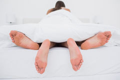 Couple making love in bed Stock Images