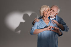 Couple making love gesture and standing in studio with heart shaped shadow Royalty Free Stock Images