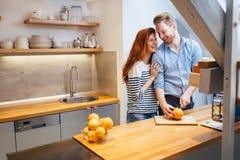 Couple making orange smoothie in kitchen Royalty Free Stock Photo