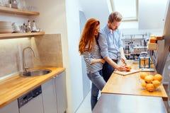 Couple making orange smoothie in kitchen Stock Photos