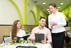 Couple making order in cafe. Young men with beautiful smiling girlfriend making order in cafe. Focus on man Stock Photos