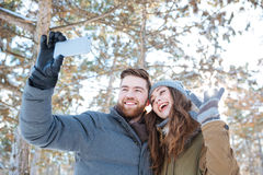 Couple making photo on smartphone in winter park Royalty Free Stock Photos