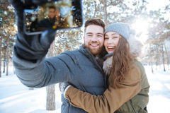 Couple making photo on smartphone in winter park Stock Photos