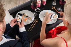 Couple Making Picture Of Food With Their Smartphones Royalty Free Stock Image