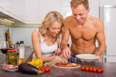 Couple making pizza together Stock Images