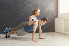 Couple making plank or push ups exercise indoors. Young couple workout in fitness club. Fitness men making plank or push ups exercise with women on back stock photos