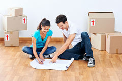 Couple making plans. Couple moving into new home looking at floor plans together royalty free stock photo