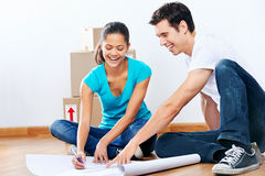 Couple making plans. Couple moving into new home looking at floor plans together royalty free stock photography