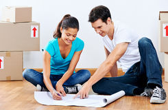 Couple making plans. Couple moving into new home looking at floor plans together Royalty Free Stock Photos