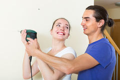 Couple making repairs in the apartment Stock Photos