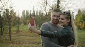 Couple making selfie in the autumn park stock video footage