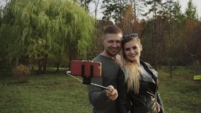 Couple making selfie in the autumn park. HD stock video