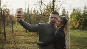 Couple making selfie in the autumn park. HD stock footage