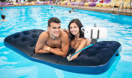 Couple making selfie photo on the phone with selfie stick on mattress in pool and on their summer vacation. Royalty Free Stock Photography