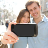 Couple making a selfie photo with a smartphone and showing screen Stock Image