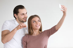 Couple making selfie portrait photo with apartment keys on smart. Portrait of happy cheerful couple just bought or rented apartment, taking selfie on smartphone Royalty Free Stock Image