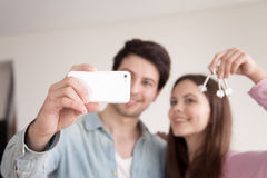 Couple making selfie on smartphone showing keys of own apartment. Young happy men and women make selfie on smartphone, holding keys of new home after buying Stock Photography