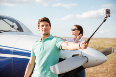 Couple making selfie standing near plane Royalty Free Stock Images