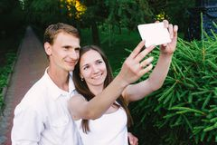 Couple making a selfie together in a green park royalty free stock photo