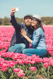 Couple making selfie in a tulip field Royalty Free Stock Images