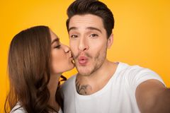 Couple making selfie, woman kissing her boyfriend in cheek. Couple making selfie, women kissing her boyfriend in cheek on yellow background royalty free stock image