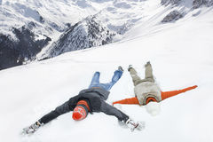 Couple making snow angels on mountain Royalty Free Stock Photography