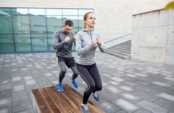 Couple making step exercise on city street bench. Fitness, sport, training, people and lifestyle concept - couple making step exercise on city street bench Royalty Free Stock Images