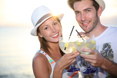 Couple making toast with cocktails on the beach Royalty Free Stock Photo