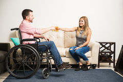 Couple making a toast with some beer. Happy men in a wheelchair making a toast with beer with his beautiful date and having fun Royalty Free Stock Photo