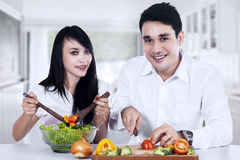 Couple making vegetables salad Stock Images