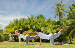 Couple making yoga balancing table pose outdoors. Fitness, sport and people concept - couple making yoga balancing table pose outdoors over exotic natural stock photos