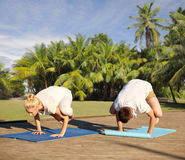 Couple making yoga crow pose outdoors Royalty Free Stock Image