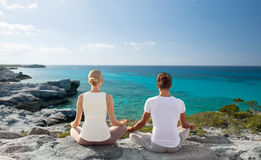 Couple making yoga exercises outdoors Stock Photo